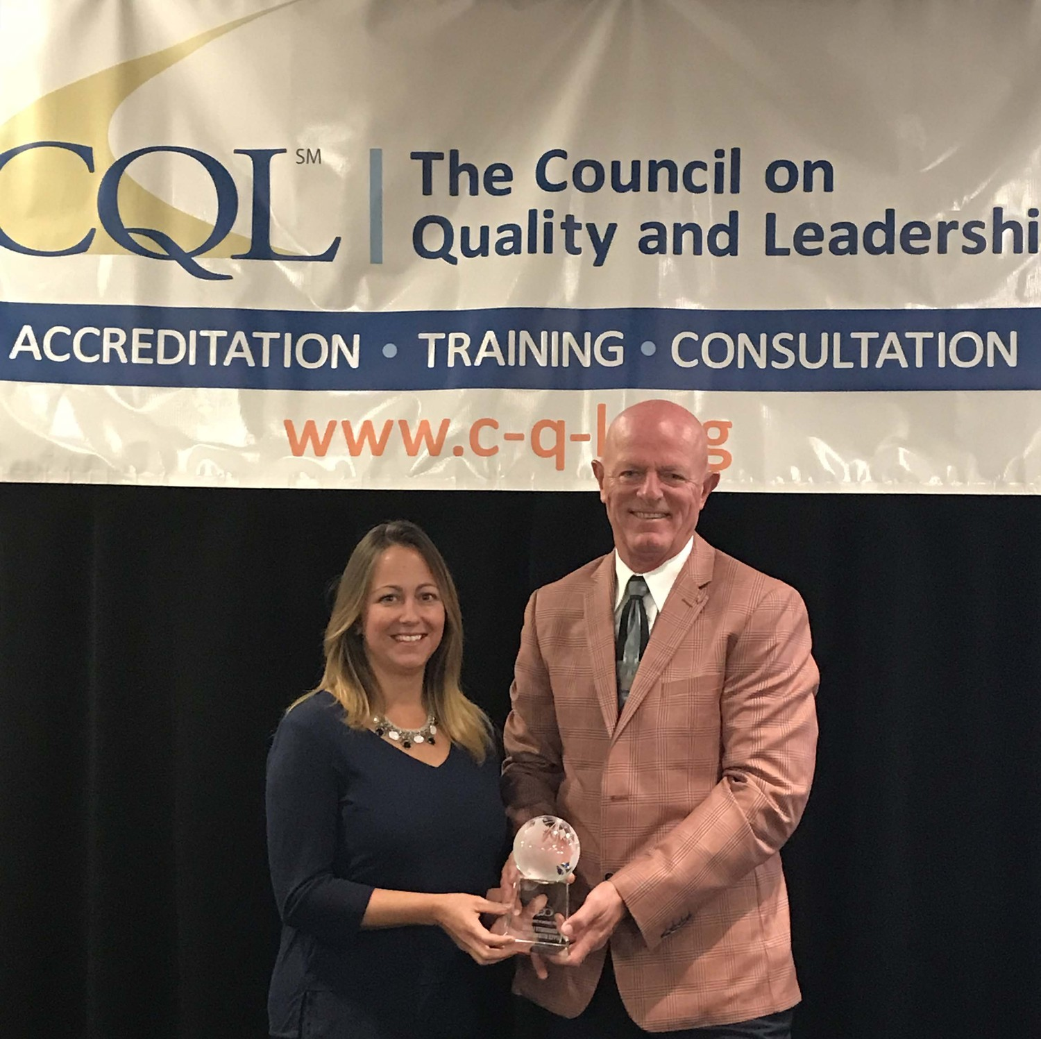 Chris Grayson, Executive Director (right) and Tina Williams, Quality Enhancement Manager (left) and accept the 2017 CQL International Award of Excellence