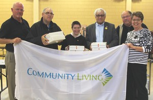 Mayor Mike Lemay accepts Community Living Flag Members of Community Living from left, Chris Grayson, ED, Stephen Gorr, Meghan Ripley, Mayor Lemay of the City of Pembroke, and Bob Smith, Holly Woermke of the Board of Directors present the Community Living Flag.